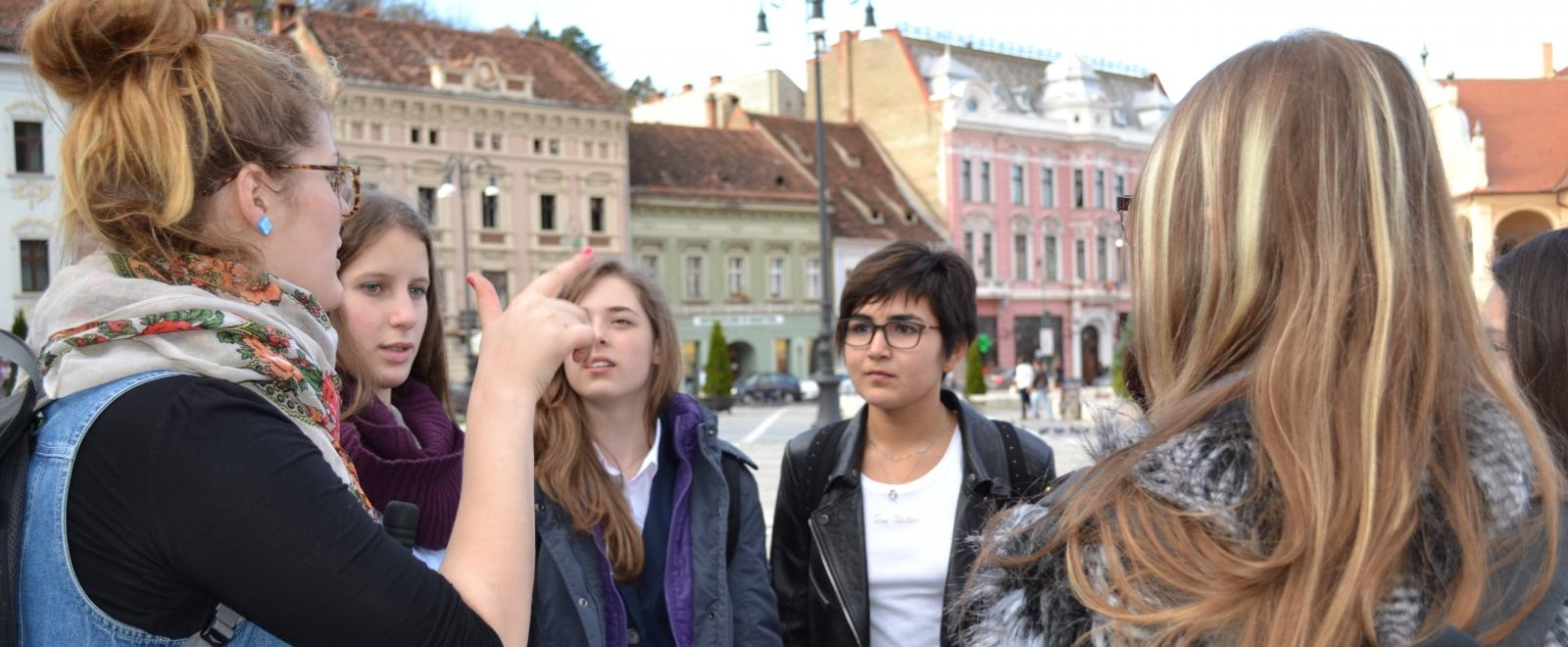 Volunteers in Romania listen to a Projects Abroad staff member during an induction tour.